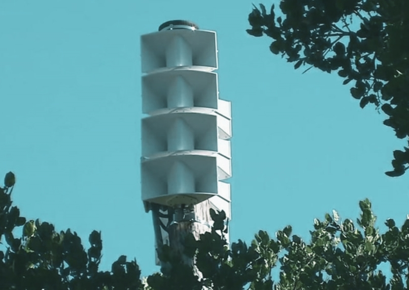 Picture of an array of horn speakers on a pole above treetops.
