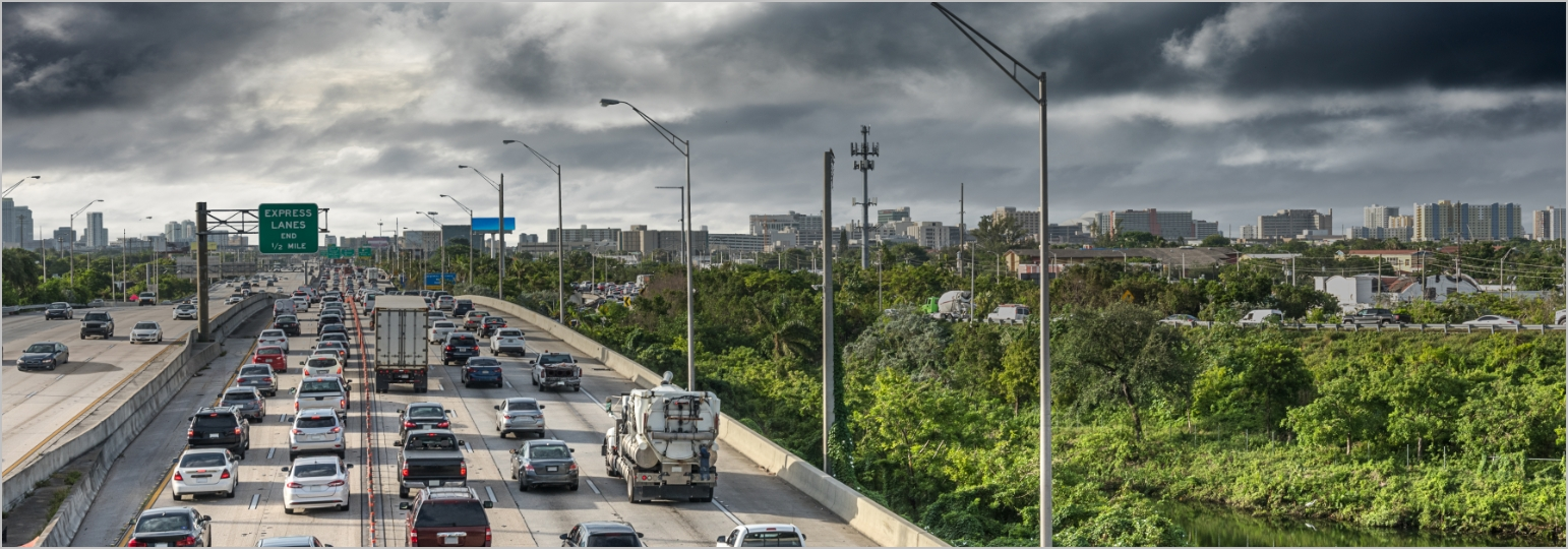 A picture of vehicles on a highway with dark stormy clouds overhead